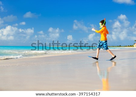 Cute boy wearing mask, snorkel and fins walking at tropical beach having fun summer vacation