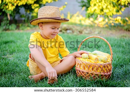 Cute boy with a basket of sweet corn