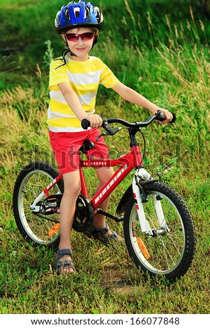 Cute boy with a bicycle outdoors.