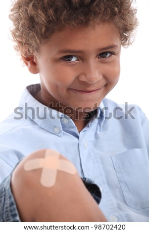 Cute boy with a plaster on his knee - stock photo
