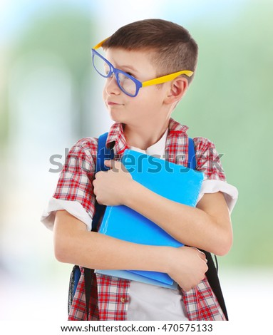 Cute boy with backpack and books on blurred background. Education concept.
