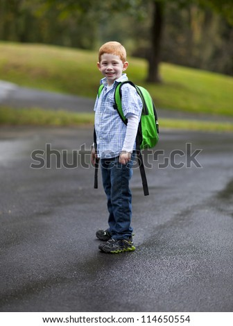 Cute boy with backpack going to school on a wet road