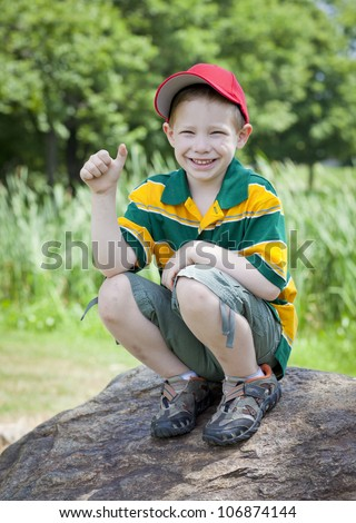 Cute boy with big smile outdoors on rock portrait - stock photo