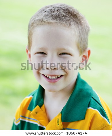 Cute boy with big smile outdoors summer portrait - stock photo