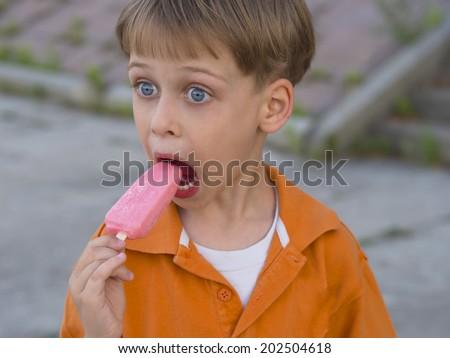 cute boy with blue eyes enjoying ice cream - stock photo