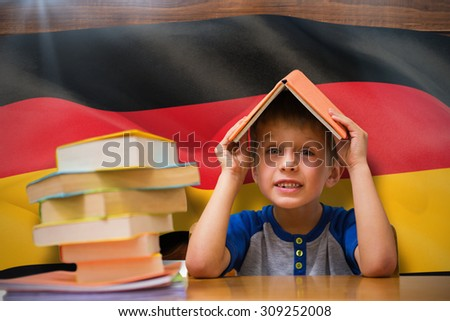 Cute boy with book on head against digitally generated german national flag - stock photo