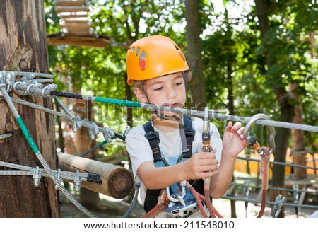 Cute boy with climbing equipment in an adventure park - stock photo