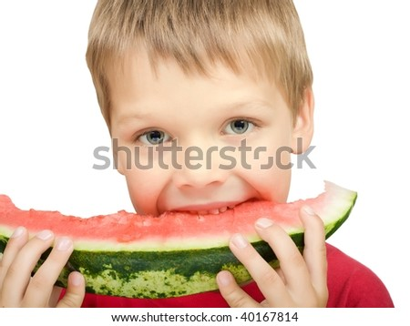 Cute boy with expressive eyes, taking a bite from a juicy watermelon