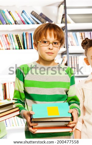 Cute boy with glasses holds books in library