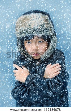 Cute boy with hat feeling cold in the winter snow - stock photo