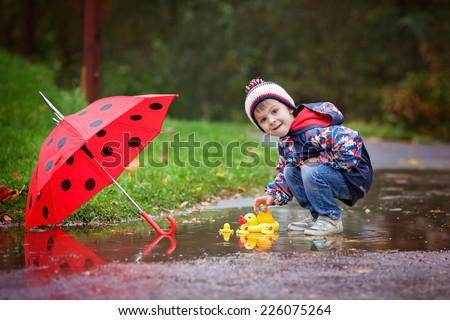 Cute boy with hat, playing with rubber ducks in the park in a puddle - stock photo