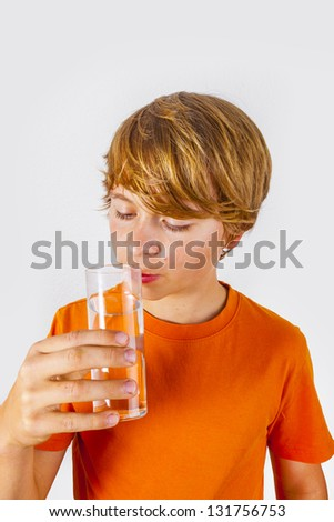 cute boy with orange shirt drinking water