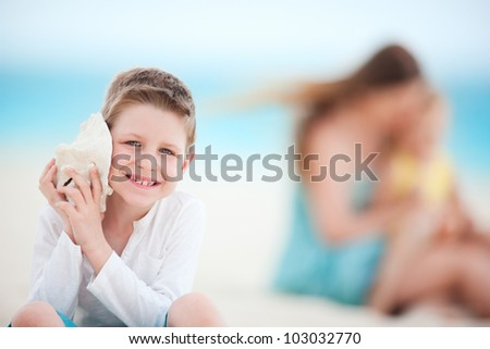 Cute boy with seashell at the beach with his family on background