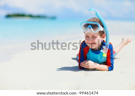 Cute boy with snorkeling equipment at tropical beach - stock photo