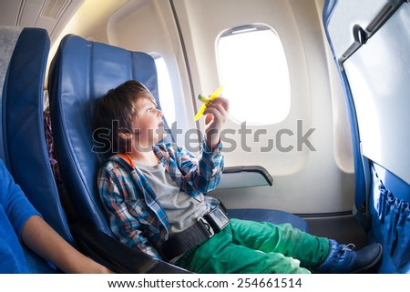 Cute boy with toy plane sit by the airplane window - stock photo
