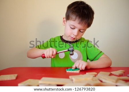 Cute boy working with hammer and nail - stock photo