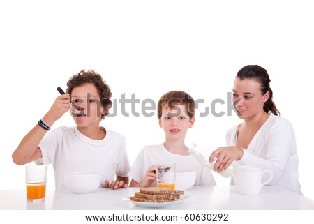 cute boys and mother taking breakfast, isolated on white, studio shot