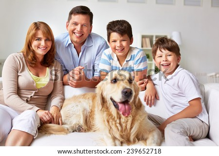 Cute boys, their parents and dog resting on sofa at home
