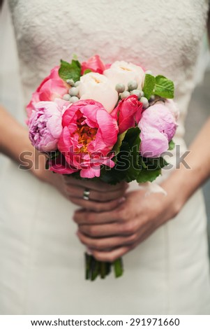 Cute bride in a white dress holding a wedding bouquet before