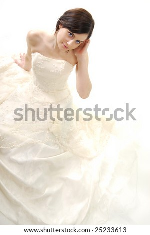 Cute bride touching her ear in a high key light - stock photo