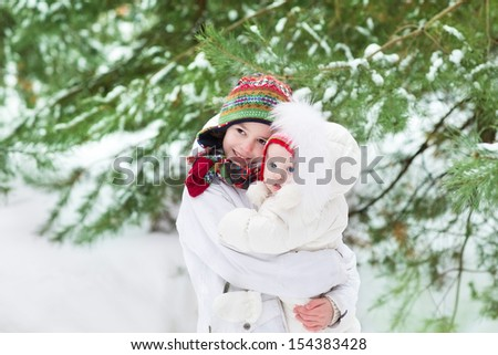 Cute brother and his baby sister wearing white snow jackets and warm winter hats are standing under Christmas trees in a beautiful snowy park - stock photo