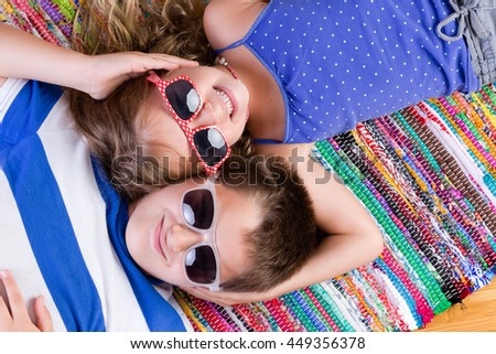 Cute brother and sister in sunglasses laying down on colorful rug while holding each others heads - stock photo