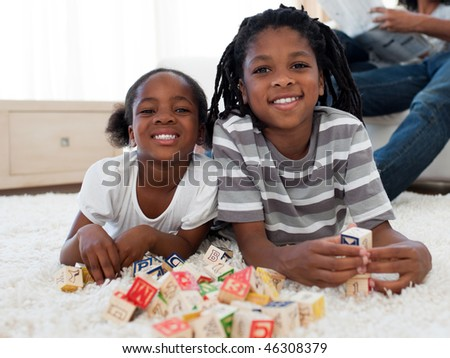 Cute brother and sister playing alphabetic cubes lying on the floor - stock photo