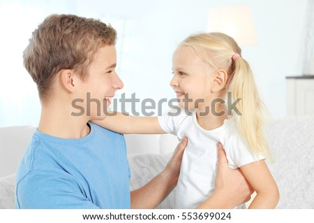 Cute brother and sister sitting on sofa in living room