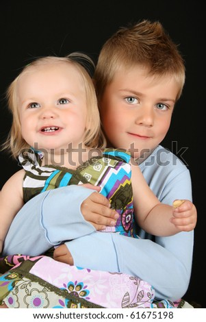 Cute brother holding his toddler sister in his arms - stock photo