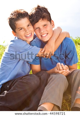 cute brothers sitting in a meadow
