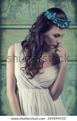 cute brunette female posing in vintage spring portrait with floral crown on the head and sensual white dress, romantic pose  - stock photo