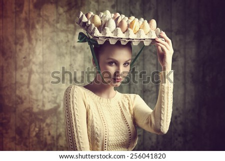 cute brunette female taking easter eggs box on the head like a bizarre hat, wearing yellow clothes and looking in camera. Funny portrait  - stock photo