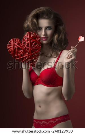 cute brunette female with stylish hair-style and make-up posing with glamour red lingerie and creative heart in the hand. Romantic sexy, valentines concept