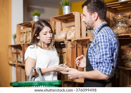 Cute brunette getting some assistance from a store clerk at a local grocery store - stock photo