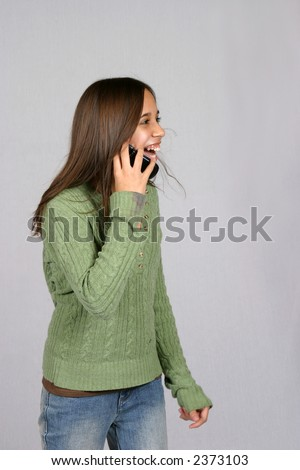 cute brunette girl on cell phone laughing - stock photo