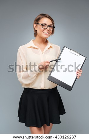 Cute brunette girl pointing at the folder isolated on the gray background