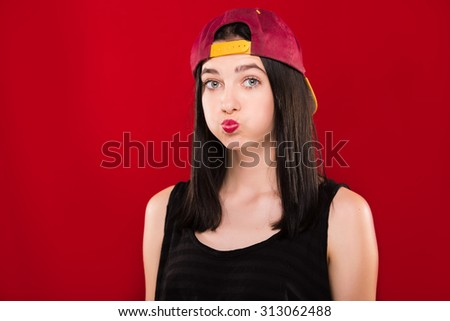 Cute brunette girl, wearing on black shirt and claret cap, standing with blown cheeks, on the red background, in studio, waist up - stock photo