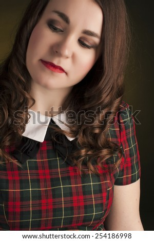 Cute brunette in tartan dress with red lips and curles - stock photo