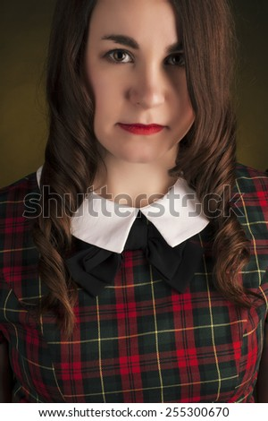 Cute brunette in tartan dress with red lips and curls - stock photo