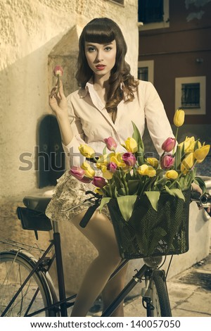 cute brunette pin-up girl  like retro fashion pin-up sitting on bicycle with colorful floral basket in and old contest - stock photo