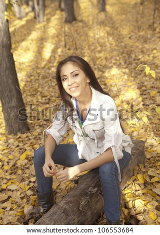 cute brunette sitting on a log in the autumn park on yellow background foliage