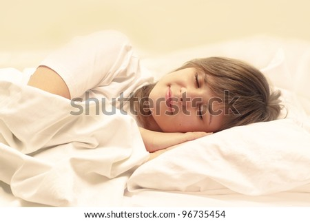 cute brunette sleeping on a white bed - stock photo