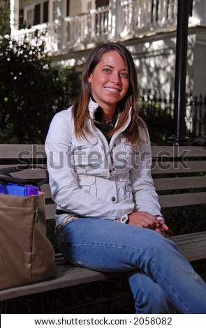 Cute brunette student on bench with books - stock photo