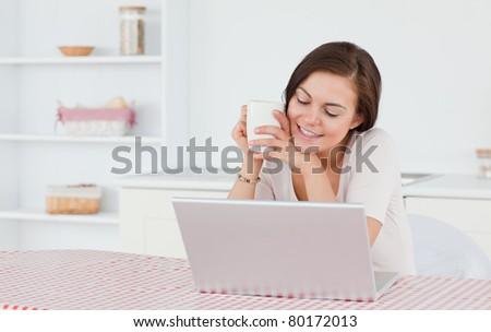 Cute brunette using her laptop and having a tea in her kitchen