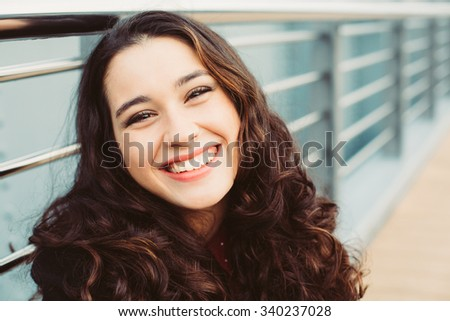 Cute brunette woman laughing in the street - stock photo