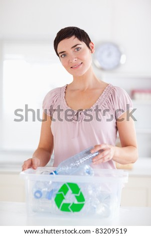 Cute brunette Woman putting bottles in a recycling box in a kitchen