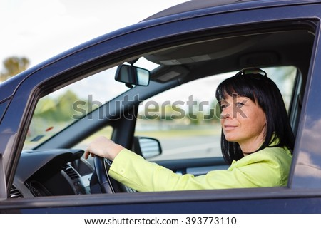 Cute Brunette Woman Sat In The Driver's Seat of Her Car with spring-summer mood. Dressed in green jacket with sun glasses on head - stock photo
