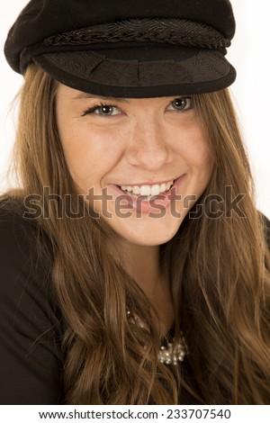 Cute brunette woman wearing black hat smiling - stock photo