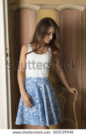cute brunette woman with long hair, golden necklace and elegant blue skirt posing in room of ancient palace near old chair and painted wall on background