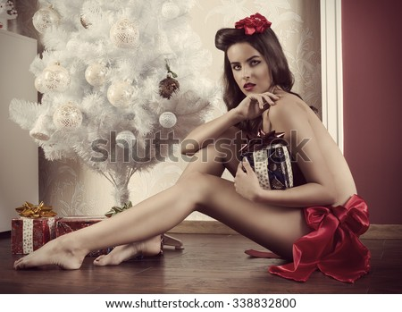 cute brunette woman with sexy body sitting naked near christmas decorated tree and wearing only red ribbon at waistline. Taking gift box in the hand and looking in camera with sexy expression  - stock photo